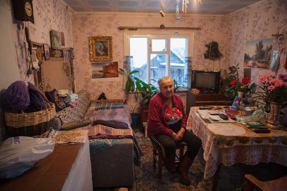 старушка в своей комнате на табуретке сидит