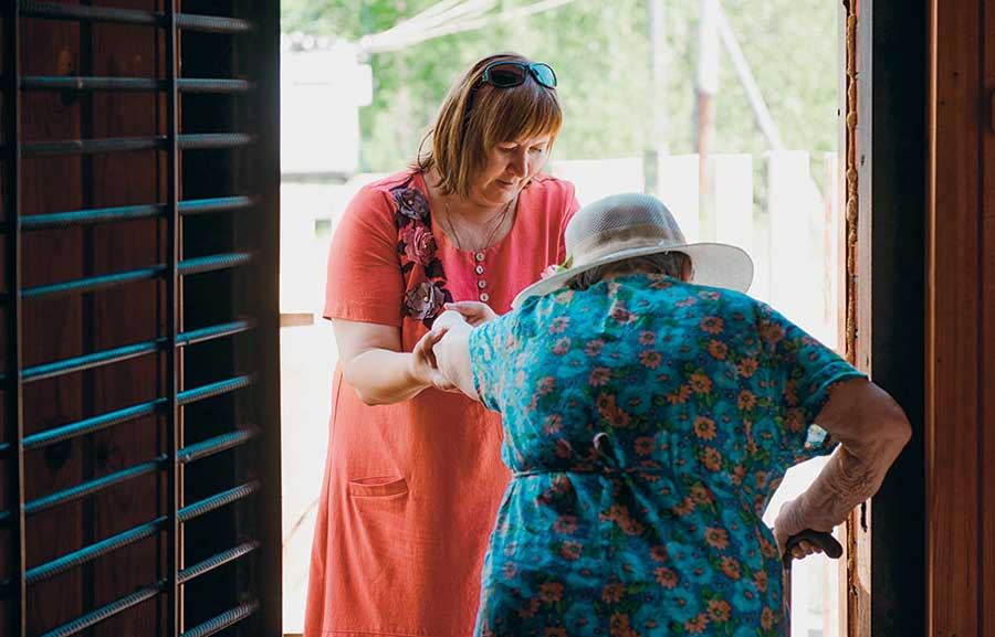 женщина помогает бабушке перейти через порог