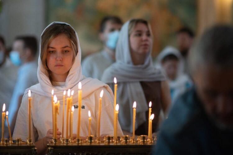 девушка у свечей молится